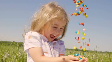 výraz : Cute little girl with pleasure catches multicolored candy falling from above. Joyful cheerful child laughing outdoors. Summer sunny day. Slow Motion.