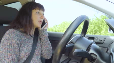 telefon : Angry woman talking on the phone in car.