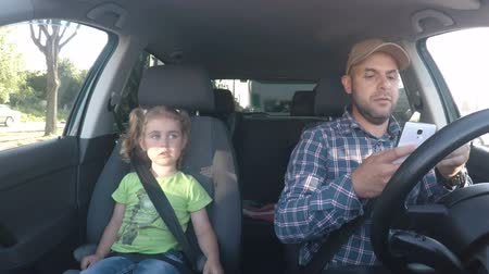 distraído : Father and his little daughter are driving in the car. Parent and child driving car having Sing a song. Bad parent uses a smartphone while driving a car. Man texting and driving in car.