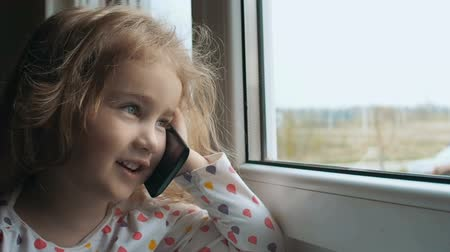 telefon : Blonde little girl talking on the phone. Sitting on the window sill. The child looks out of the window. Girl talking on the phone near the window