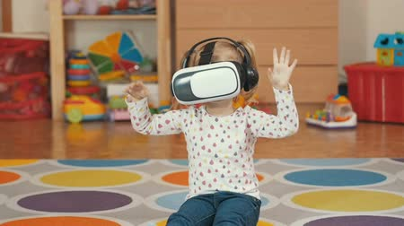 şaşırtıcı : Girl wearing virtual reality goggles. Virtual reality game. The little girl with surprise and pleasure uses head-mounted display.