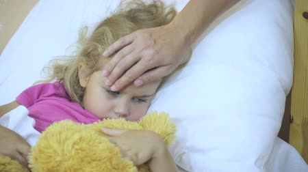 doente : Sick little girl having her temperature. Child with a fever: Woman stroking the childs head. Close-up. Stock Footage