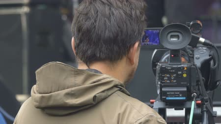 camera operator : Director looking at a camcorder. Operator work with equipment.