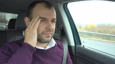 stres : Tired and stressed businessman is sitting in the car. Man having headache. Wideo