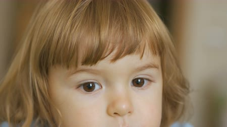 baby chubby : Young child and emotions, portrait of serious kid. Sad boy with blond hair looks at the camera. Little plump baby. Face close up. 4K UHD Stock Footage