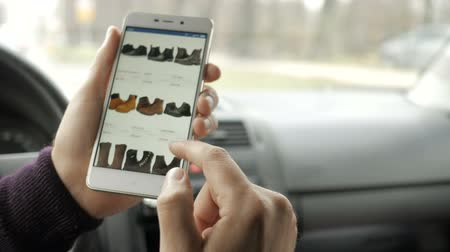 footgear : A man looks at the goods in the online store, sitting in the car. Smart phone online shopping.