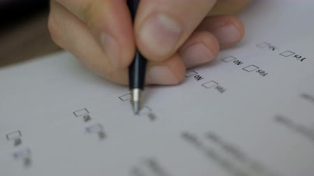 questionário : Hand filling yes and no at the checklist box. Close up. survey and poll. Filling of questionnaire a person by a ball point pen. Stock Footage