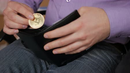 cüzdan : A businessman in a purple shirt takes a gold bitcoin from his purse with a gold coin. Cryptocurrency in the mans hand.