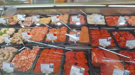 raf : Selling a piece of meat in the store. Selection of different cuts from fresh meat raw red in a supermarket.