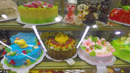 brulee : Window of a cake shop with a variety of cakes on display. Pies and cakes Dessert store. Pastry shop with donuts, muffins, creme brulee, cakes with fruits and berries