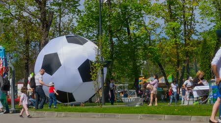 воздушный шар : People in day festival in city park. Time lapse. Crowd of tourists go for a summer day near a big soccer ball. Timelapse. Стоковые видеозаписи