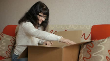 изумление : The girl opens the parcel from the online store. Young woman looks in the box, is surprised and happy to receive a surprise. Girl opened a box with a gift. Slow Motion.