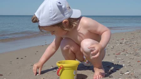 sicília : Little blond boy playing on the beach. The child walks on the sand on the ocean, playing with sand and toys. Stock Footage