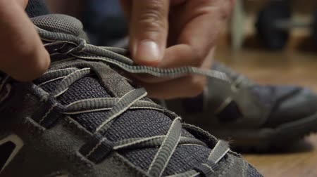затянуть : Closeup tying shoelaces on sneakers. Athlete tied up shoelaces, running shoes. Close up. Slow motion. Стоковые видеозаписи