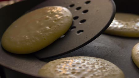 nalesniki : Cooking pancakes on special pan in the kitchen at home. Slow motion. Closeup.