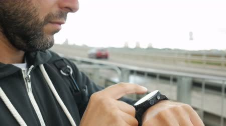 his : Man using his smart watch device. Results of a running training session on smartwatch. Guy using gadget, standing near a highway on the outskirts of the city of New York.