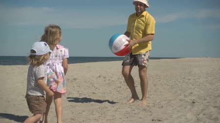 lánya : Father enjoying playing ball with young little kid on beach. Family Summer Beach Vacation. Slow Motion. Children play with dad on the beach.