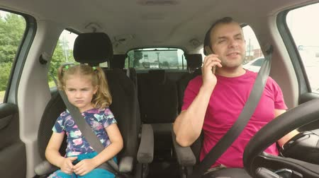 riskli : Father and his little daughter are driving in the car. A bad parent uses a smartphone while driving a car. Man talking on the phone while driving with his daughter in the car. Stok Video