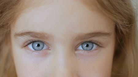 закрывать : Portrait of little girl with blue eyes looking at camera. Young serious kid looking at camera. Closeup Стоковые видеозаписи