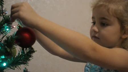 bombki : Happy kid decorate Christmas tree. Little girl decorating christmas tree with toys and balls.