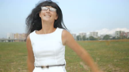 kifejező pozitivitás : Successful business woman dances and rejoices outdoors on the outskirts of New York City. Funny Businesswoman Dancing. The girl in white dress rejoices. 4K UHD.