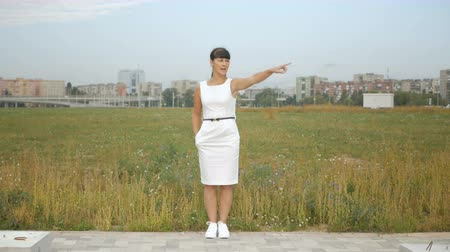 exibindo : Businesswoman stands on the outskirts of the city and directs. Young woman with her hand.