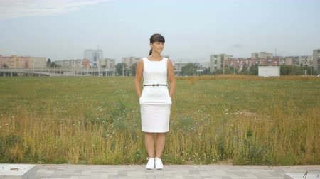 observing : Young single woman in a white dress is standing alone on the outskirts of the city of New York. 4K UHD. Stock Footage