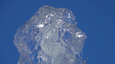 aqua park : A splash of clear ice water. Closeup of a light splashing water in a sunny fountain in a park in summer on a blue sky background. Water flow of a fountain fly up in air with many splashes. Slow motion. Stock Footage