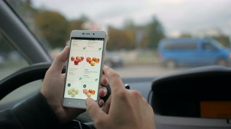 ananas : A man looks at the online grocery store, sitting in the car. apple Smartphone online shopping.