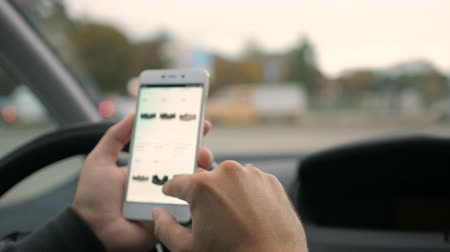 footgear : Online store, sitting in car. Driver, sitting in the car. The screen is blurred. Focus on the finger hand. Stock Footage