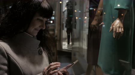 qr : Shopping at the mall, sales time. Woman on the street. Beautiful attractive woman near shop window with mannequins. Reading bar codes by smartphone.