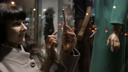 qr : Shopping at mall, sales time. Woman looking at the street and taking a photo. Woman near shop window with mannequins. Reading bar codes by smartphone.