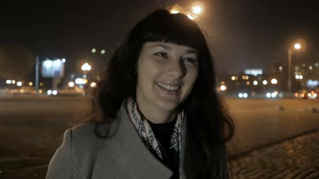 seducing : Portrait of a Beautiful Young Woman at Night in the City. Girl Pretty woman smiling at camera.