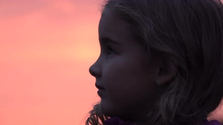 umutlu : Kid looking up at the sky in nature. Little girl praying looking up at purple sky with hope, close-up. Stok Video
