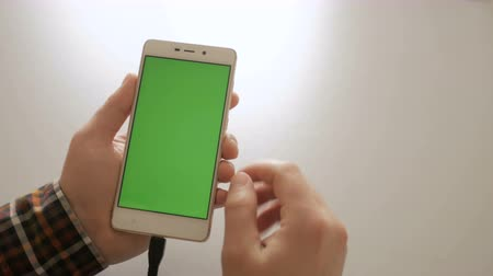 adapter : Man using smartphone with green screen. Smart phone charging in USB connection for hands - USB data cable connecting on modern gadget. Chroma key. Green screen.