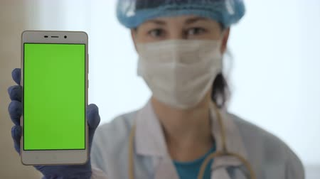 kimyager : Close up of green screen on phone held by scientist. Woman holding phone with compositing. Female medical professional displaying mobile smartphone with greenscreen. Stok Video