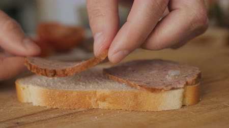 sekaná : Close up. Man cooking sandwich on wooden table. Slow motion.
