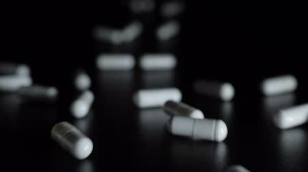 nutritional supplement : Tablets on a black background. Pills. Medicine and healthy. Close up of capsules. Many white medical capsules falling down. Slow motion. Closeup.