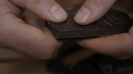amargo : Man breaks chocolate bar. Slow motion. Close up. Hands break a bar of chocolate. Closeup. Stock Footage
