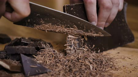 grated : Chopped dark chocolate on kitchen board. Chopping a Bar of Chocolate While Making Baking. Slow motion. Close up. Chop on wooden board. Closeup. Stock Footage