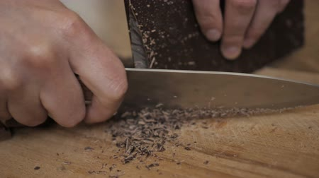 amargo : Chopped dark chocolate on kitchen board. Chopping a Bar of Chocolate While Making Baking. Slow motion. Close up. Chop on wooden board. Closeup. Stock Footage
