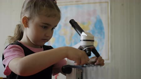 kimyager : Little girl in science lab study samples under microscope. Schoolgirl looking through microscope in science class. Child looking into a microscope, studing biology, chemistry in school laboratory. Stok Video