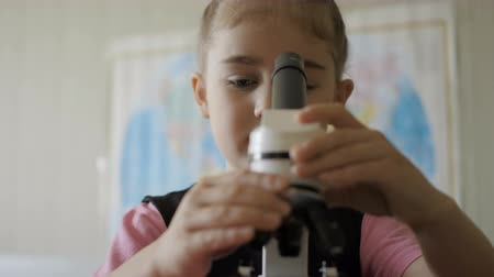 образец : Little girl in science lab study samples under microscope. Schoolgirl looking through microscope in science class. Child looking into a microscope, studing biology, chemistry in school laboratory. Стоковые видеозаписи