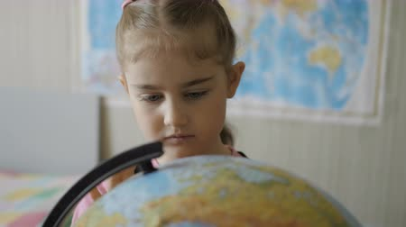 zvědavý : Elementary school. Travel planning. Little girl looking at the globe Student Child Studying Earth Globe in Library. Closeup. Dostupné videozáznamy