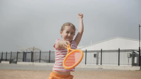 medaille : Little girl with tennis club Active exercise for kids. Summer activities for children. Child learning to play tennis. Happy 7 year old girl jumping. Slow motion.