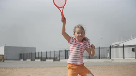 medal : Little girl with tennis club Active exercise for kids. Summer activities for children. Child learning to play tennis. Happy 7 year old girl jumping. Slow motion.