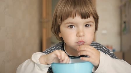 corn flakes : Little boy having breakfast at home. Pretty American boy eating cereal with appetite. Child having breakfast in the kitchen. Closeup.