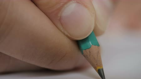 grafito : Artists hands drawing wooden pencil writes on paper. Notebook paper. Closeup. UHD 4K.