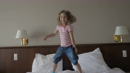 neşeli : Happy child little girl jumping on the bed, happy family concept slow motion. 4K UHD. Child girl having fun jumps and plays in bedroom. Stok Video