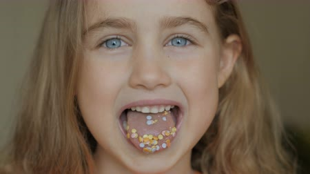 jeść : Full of candy. Little girl eating candy. Child eating chicle. Close up portrait of silly girl with wavy hair sticking out tongue shaped candy pieces on tip.